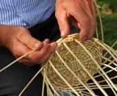 Elder's hands working the cane to create a wicker basket — Stockfoto