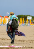 Abusive Peddler with fabrics and dresses walking on the beach — Stock Photo