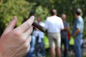 Hand with cigar and many people in the background out of focus — Stock Photo