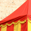 Yellow and red lines tent near the wall of castle — Stock Photo #55382151