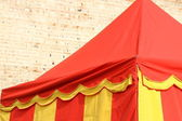 Yellow and red lines tent near the wall of castle — Stock Photo