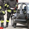 Постер, плакат: Firefighters open the car with a pneumatic shears