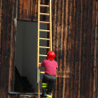 Постер, плакат: Fireman during a demonstration of using the ladder to reach the