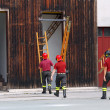 Firefighters during the fire drill mount a ladder — Stock Photo #55508385