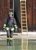 Fireman with the uniform wet after the fire-fighting Services tu — Stock Photo