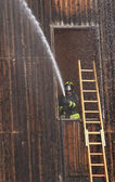 Fireman extinguish a fire with a hose — Stock Photo