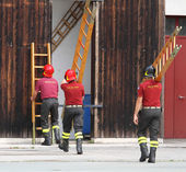 Firefighters during the fire drill mount fast wooden ladder — Stock Photo