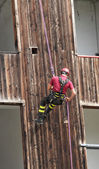 Firefighter climbing during the ascent abseiling from a building — Stock Photo
