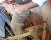 Elderly man skilled strawbedder line of old wood and rattan chai — Stockfoto