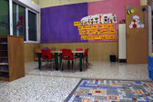Preschool classroom with red chairs and table — ストック写真