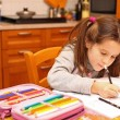 Young girl writes with pencil on the school book in the kitchen — Stock Photo #62687467