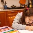 Pretty girl writes with pencil her homework in the kitchen — Stock Photo #62687605