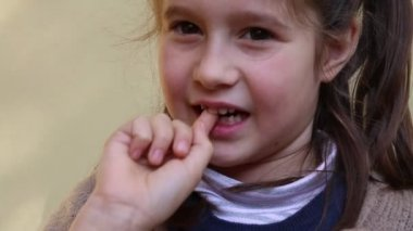 Little girl with the tooth that dangles by her hand — Stock Video