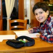 Young smiling boy does homework at his home — Stock Photo #63287379