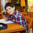 Smiling boy does homework at his home — Stock Photo #63287395