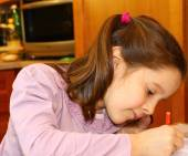 Little girl writes on her notebook at home — Stock Photo