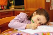 Thoughtful young girl writes on her notebook — Stock Photo
