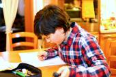 Young boy writes on his notebook and remote in his hand — Stock Photo