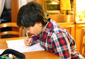 Boy does homework at his home — Stock Photo