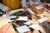 Fishmonger sells the fresh fish at the market — Stock Photo
