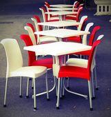Chaises rouges et blancs avec des tables dans un café en plein air sur la route — Photo