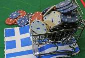 Shopping cart full of casino chips over the flag of Greece — Stock Photo