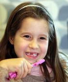 Jovem sem um dente enquanto escova os dentes no banheiro — Fotografia Stock