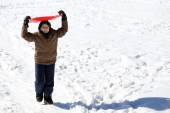 Young boy walks with tobogganing on the head on fresh snow — Foto de Stock