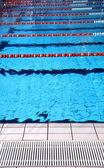 Piscina interior com água azul e as pistas de natação — Fotografia Stock