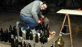 Man pour wine from the demijohn to glass bottles — Stock Photo
