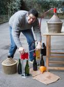 Man white bottling red wine from the demijohn — Stock Photo