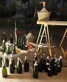 Pour the wine in the backyard with the Carboy and glass bottles — Stock Photo