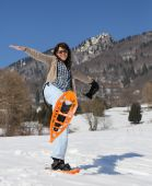 Beautiful woman with snowshoes in snowy mountain — Stock Photo