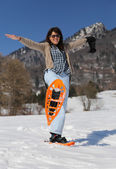 Pretty woman with snowshoes in snowy mountain — Stock Photo