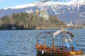 Rowboats moored on the shore of Lake Bled and medieval castle — Stock Photo