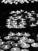 Many lit candles at mass in church — Stock Photo