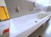 Ceramic sink with many taps in the school — Stock Photo