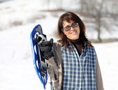 Pretty woman with snowshoes in the mountains in winter — Стоковое фото