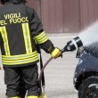 Firefighter in action with foam to put out the fire — Stock Photo #72768973