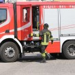 Постер, плакат: Italian firefighters during an emergency with protective suits a