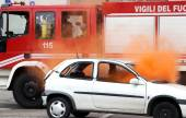 Fire on a car and engine intervention of firefighters — Stock Photo