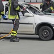 Постер, плакат: Brave firefighters relieve an injured after a road accident