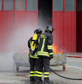 Firefighters with oxygen bottles off the fire during a training  — Stock Photo