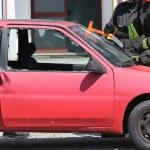 Постер, плакат: Firefighter cuts the windshield of car with a Hacksaw