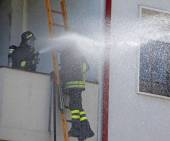 Firefighter sprays water with the spear fighting — Stock Photo