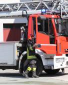 Fireman and a firetruck in the barracks of the fire brigade — Stock Photo
