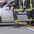 Постер, плакат: Firefighters relieve an injured after a road accident