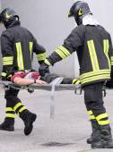 Two firefighters carried the injured away on stretchers — Stock Photo