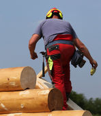 Carpenter with helmet and protective equipment on the roof of th — Stock Photo