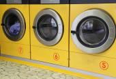 Three yellow washing machines in laundromats — Stock Photo